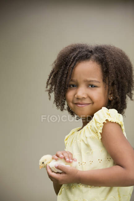 Girl holding a baby chick. — Stock Photo
