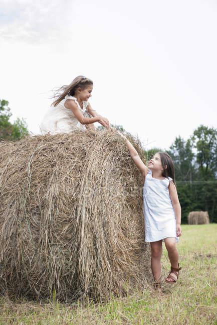 Niñas jugando por un gran haybale - foto de stock