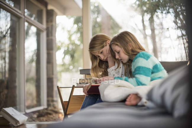 Two girls reading book on sofa. — Stock Photo