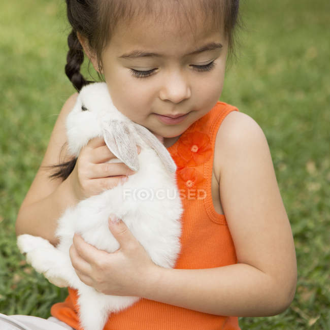 Child holding white rabbit — Stock Photo