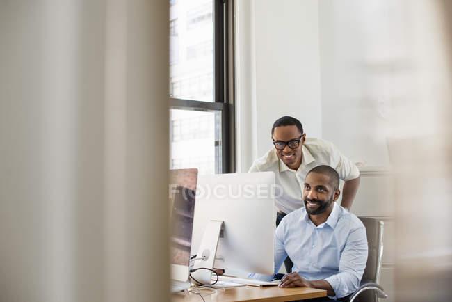 Männer auf der Suche auf einem Computer-Bildschirm — Stockfoto