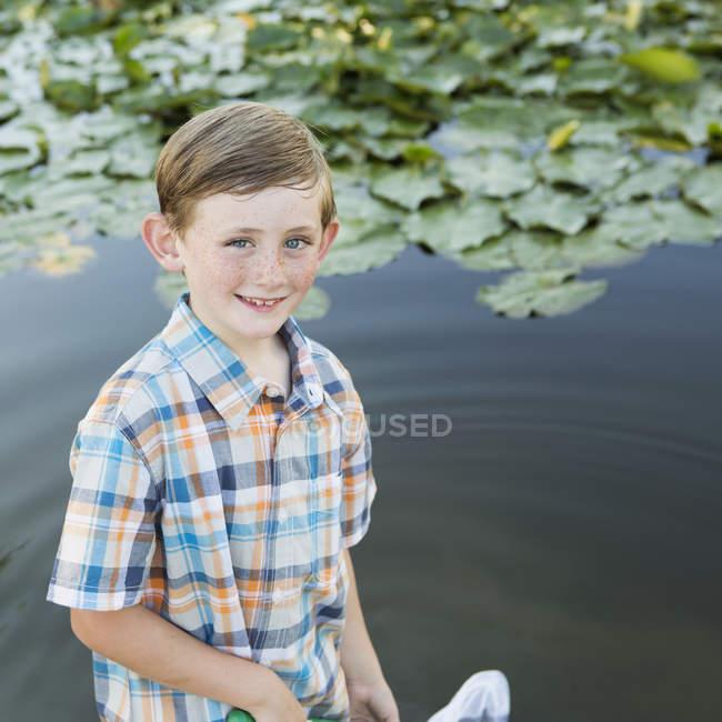 Garçon debout en eau peu profonde — Photo de stock