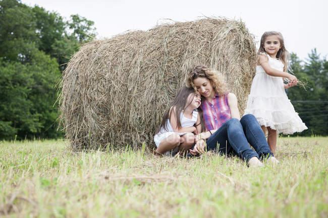 Madre al aire libre con sus hijas. - foto de stock