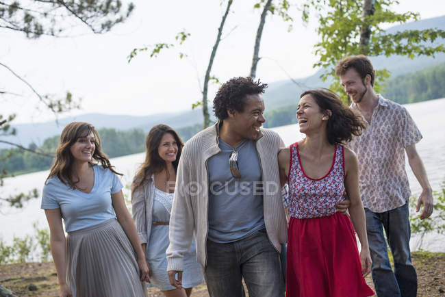 People enjoying walk by lake — Stock Photo