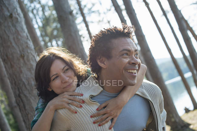 Couple hugging in shade of trees — Stock Photo