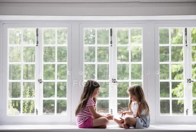 Meninas, sentada no peitoril da janela — Fotografia de Stock