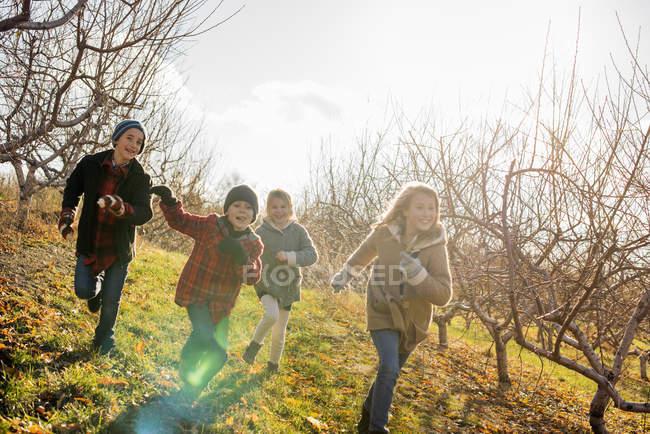 Four children running outdoors — Stock Photo