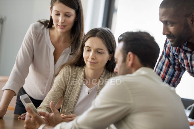 Чотири людей навколо цифровий планшетний — стокове фото