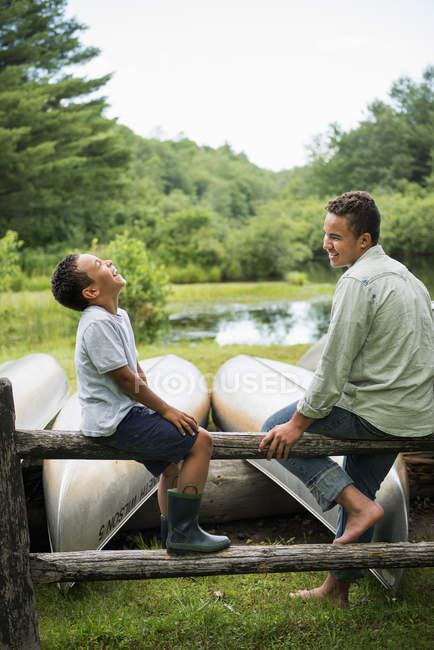 Hermanos jugando junto a un lago. - foto de stock