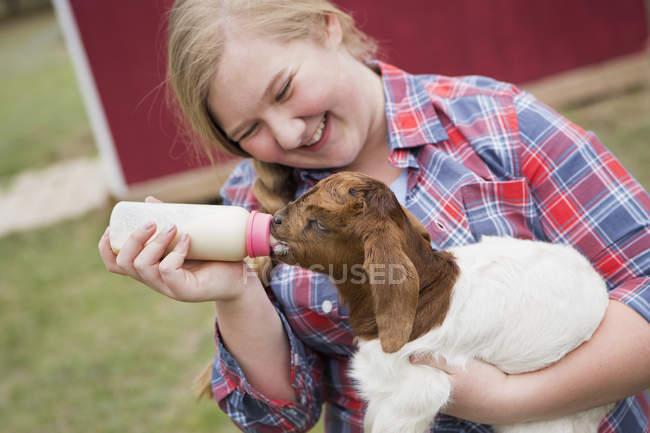 Girl feeding a baby goat. — Stock Photo