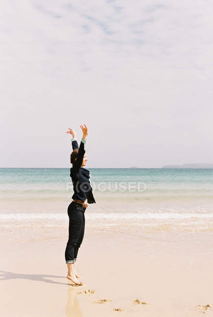 Woman standing barefoot on the sand — Stock Photo