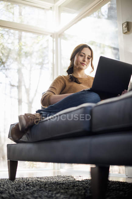Woman sitting on sofa and looking at laptop — Stock Photo