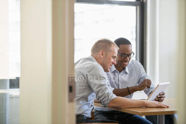 Men looking at a digital tablet. — Stock Photo