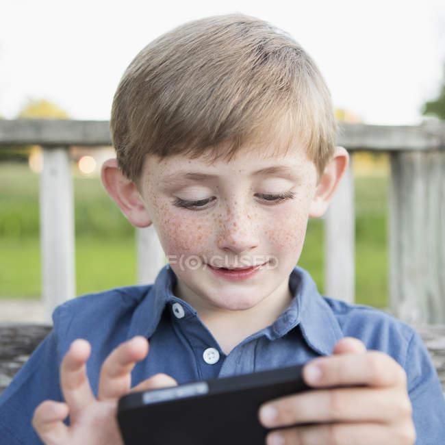 Ragazzo che gioca con lo smartphone — Foto stock