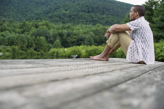 Man sitting on a wooden pier by a lake — Stock Photo