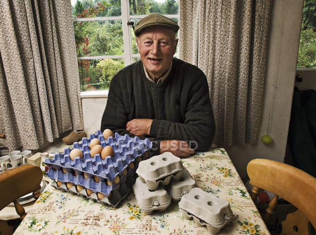 Farmer in a farmhouse with trays of fresh eggs. — Stock Photo