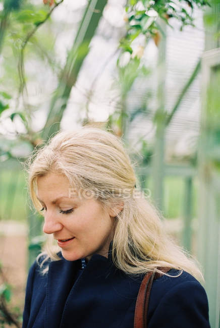 Blonde woman in a conservatory — Stock Photo