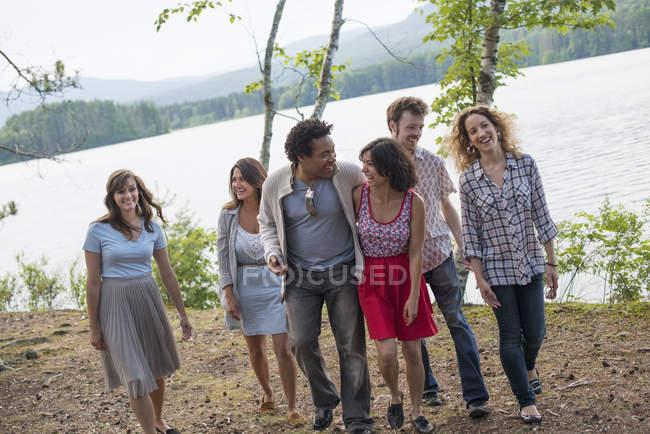 Les gens qui aiment marcher au bord du lac — Photo de stock