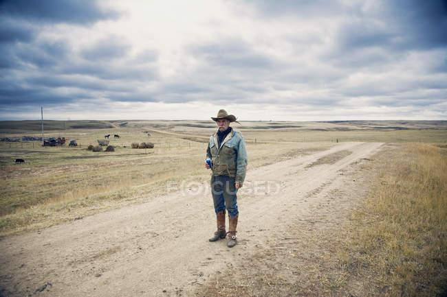Ковбой, стоящий на проселочной дороге — стоковое фото
