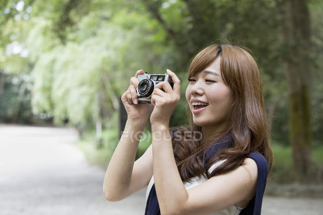 Woman in park holding camera — Stock Photo