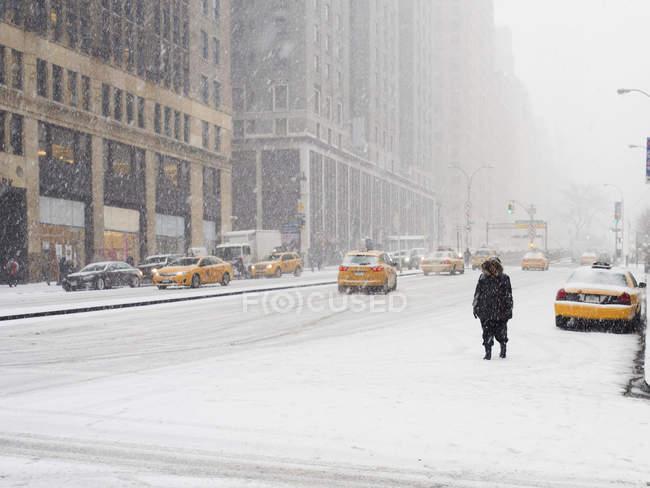 Mann geht in eine Stadt im Schnee — Stockfoto