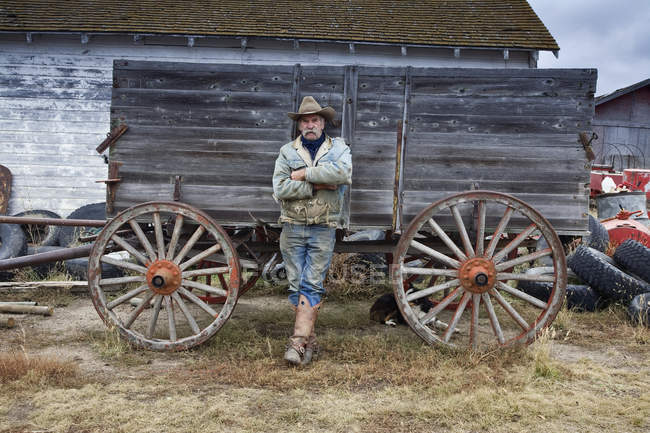 Cowboy leaning against wooden wagon — Stock Photo