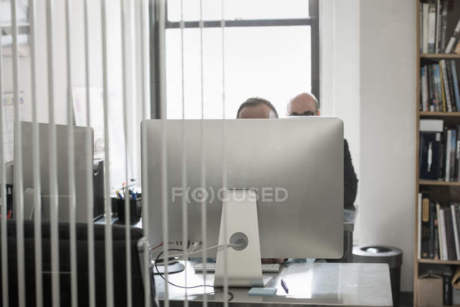 Two people behind a computer terminal. — Stock Photo