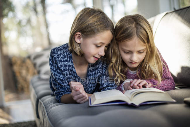 Girls looking at book on sofa — Stock Photo
