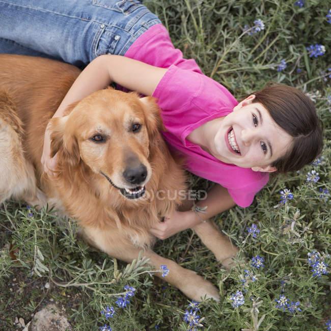 Дівчинка обіймає золотистий ретрівер ПЕТ. — стокове фото