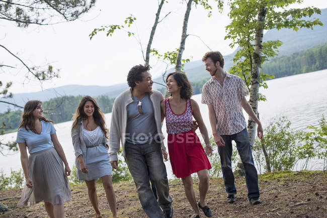 People enjoying walk by lake — Stock Photo