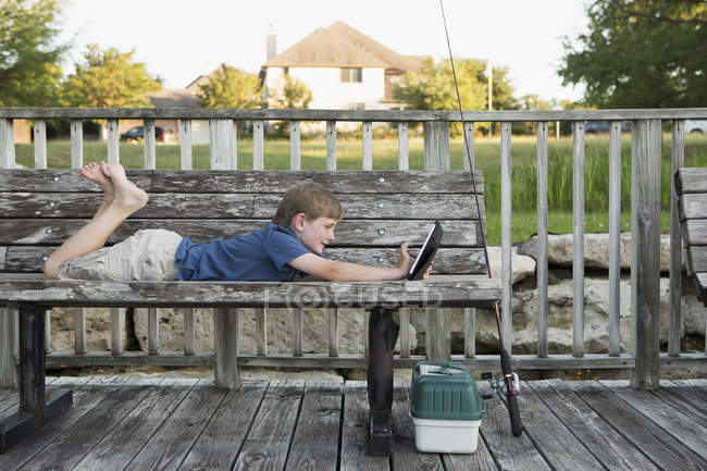 Boy on bench using a digital tablet. — Stock Photo