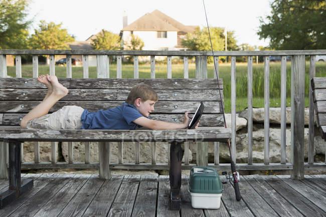Ragazzo in panchina utilizzando un tablet digitale . — Foto stock