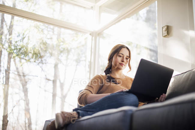 Woman on sofa looking at laptop — Stock Photo