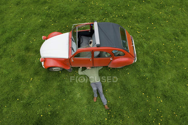 Man inspecting the underside of the car. — Stock Photo
