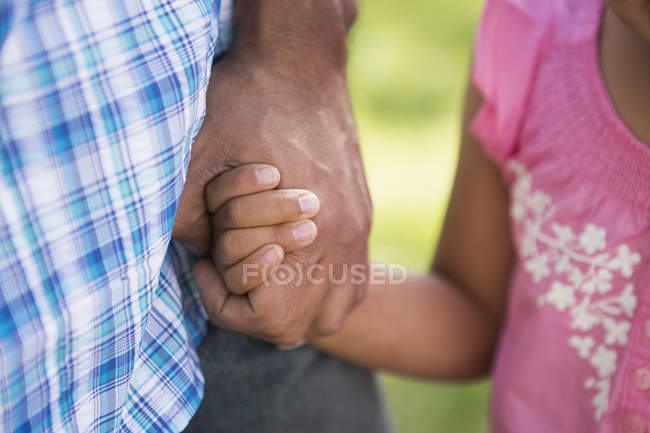Young child holding father's hand. — Stock Photo