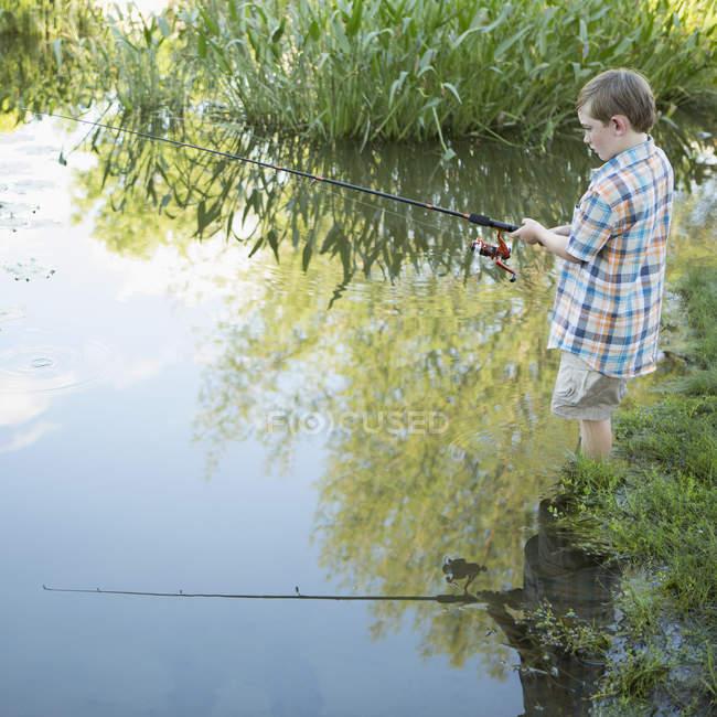 Jovem rapaz pescando em águas calmas — Fotografia de Stock