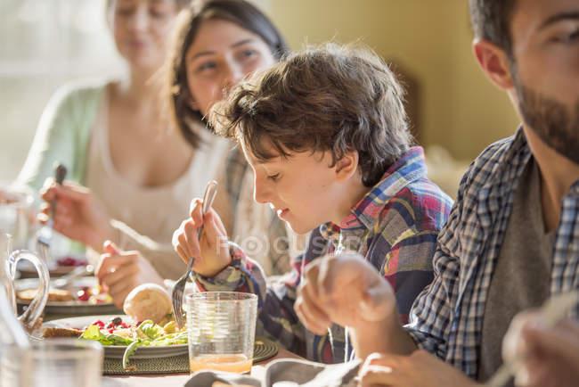 Adultos e crianças, sentados à volta de uma mesa — Fotografia de Stock