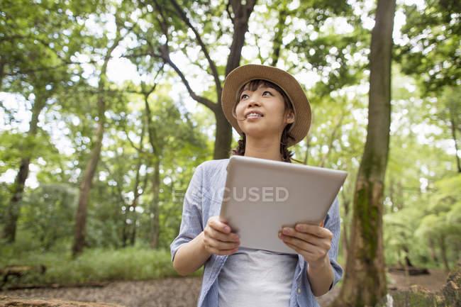 Жінка тримає цифровий планшетний в лісі. — стокове фото