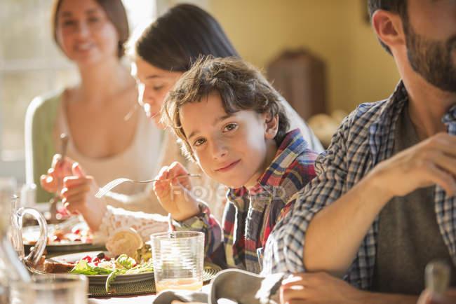 Adultos e crianças sentados em torno de uma mesa — Fotografia de Stock