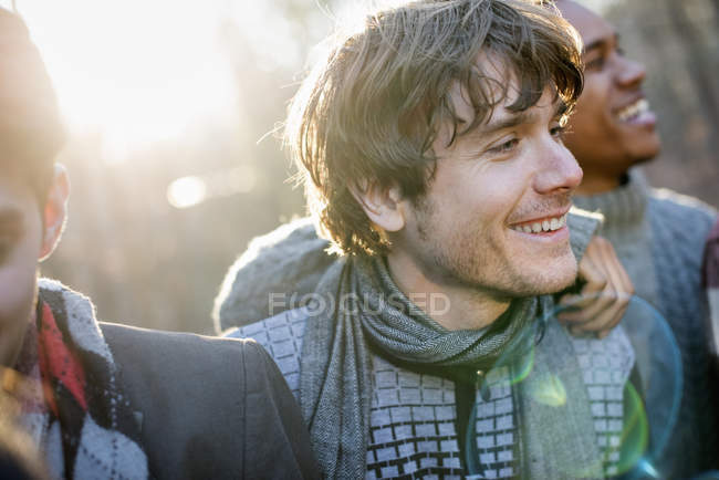 Smiling men in sunlit forest — Stock Photo