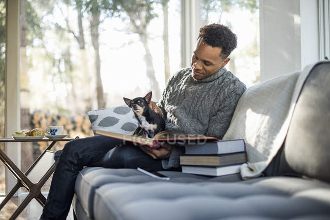 Man sitting on sofa with dog — Stock Photo