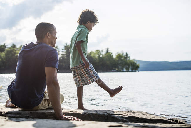 Pai e filho em uma margem do lago — Fotografia de Stock