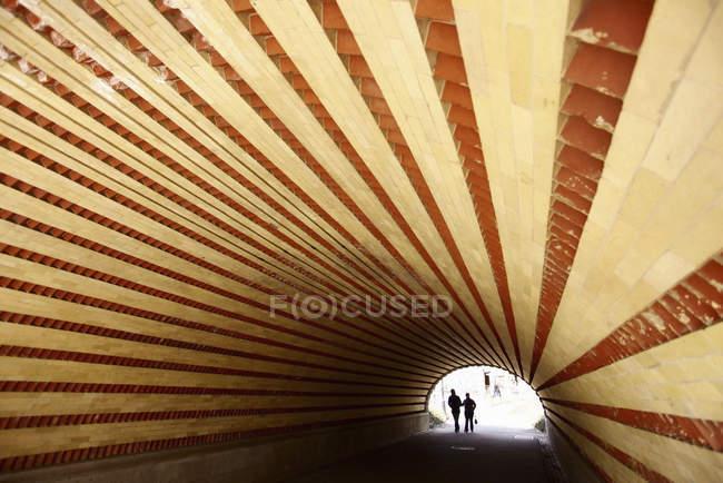 Пара, идущая через туннель — стоковое фото
