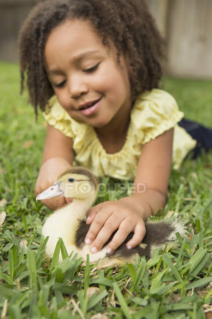 Girl petting duckling — Stock Photo