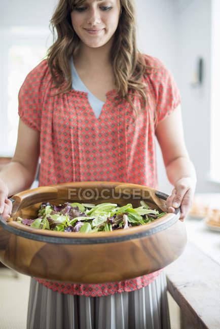 Mujer llevando comida a una mesa - foto de stock