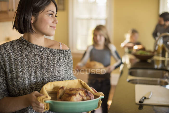 Woman and two girls carrying food — Stock Photo