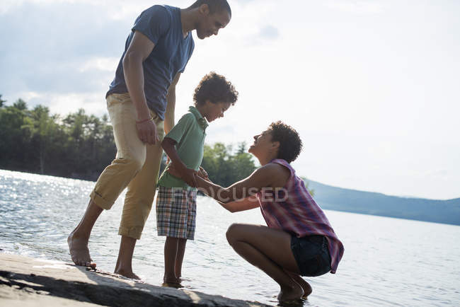 Parents and son spending time by a lake — Stock Photo