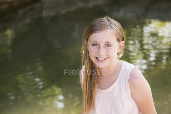 Young girl by a stream. — Stock Photo