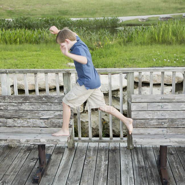 Мальчик прыгает с одной скамейки на другую — стоковое фото