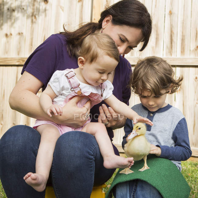 Woman and children with duckling. — Stock Photo